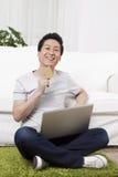 Uomo d'affari facendo uso di un computer portatile su tappeto Immagini Stock Libere da Diritti