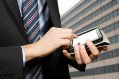 Uomo d'affari facendo uso di un dispositivo dello schermo attivabile al tatto Fotografia Stock Libera da Diritti