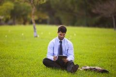 Uomo d'affari facendo uso di una compressa digitale Immagini Stock