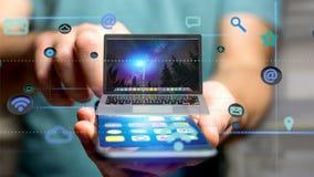 Uomo d'affari facendo uso di uno smartphone con un computer che circonda dal ap Immagine Stock