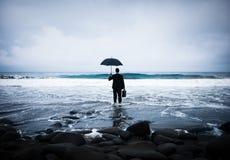 Uomo d'affari Facing Storm sulla spiaggia immagine stock libera da diritti