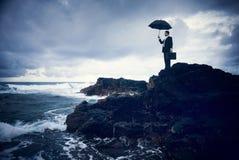 Uomo d'affari Facing Storm sulla spiaggia fotografie stock libere da diritti