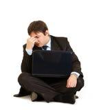 Uomo d'affari faticoso che si siede sul pavimento con il computer portatile Fotografie Stock Libere da Diritti