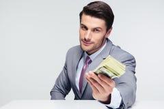 Uomo d'affari felice che dà soldi sulla macchina fotografica immagini stock libere da diritti
