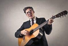 Uomo d'affari felice che gioca la chitarra Fotografie Stock Libere da Diritti