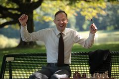 Uomo d'affari felice che gioca scacchi Fotografia Stock