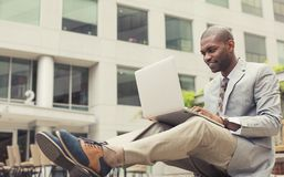 Uomo d'affari felice che lavora al computer portatile all'aperto Fotografia Stock