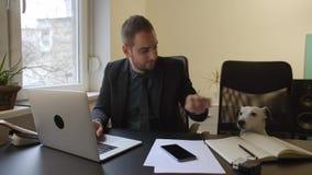 uomo d'affari felice che lavora al computer portatile in ufficio che si siede accanto al cane con un legame stock footage