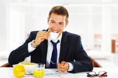 Uomo d'affari felice che mangia prima colazione all'ufficio Fotografie Stock Libere da Diritti