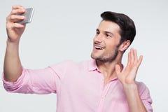 Uomo d'affari felice che mostra il segno di saluto sullo smartphone Immagine Stock Libera da Diritti