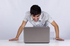Uomo d'affari felice che osserva al suo computer portatile Fotografia Stock Libera da Diritti