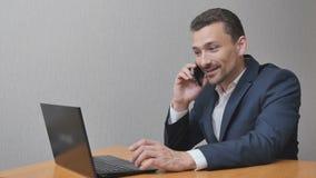 Uomo d'affari felice che parla sullo smartphone archivi video