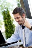 Uomo d'affari felice che passa in rassegna sul Internet fotografia stock