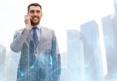 Uomo d'affari felice che rivolge allo smartphone in città Immagine Stock