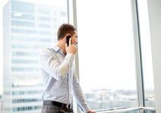 Uomo d'affari felice che rivolge allo smartphone in ufficio Fotografia Stock Libera da Diritti