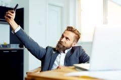 Uomo d'affari felice che si siede alla tavola e che fa la foto del selfie sullo smartphone in ufficio Fotografia Stock Libera da Diritti