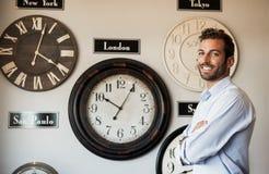 Uomo d'affari felice che sta accanto alla parete degli orologi internazionali Fotografie Stock Libere da Diritti