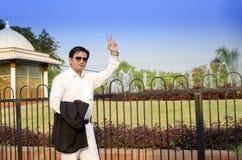 Uomo d'affari felice che sta mostrante segno vicotry Fotografie Stock Libere da Diritti