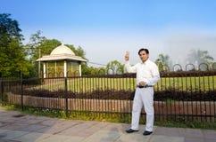 Uomo d'affari felice che sta mostrante segno vicotry Fotografia Stock