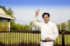 Uomo d'affari felice che sta mostrante segno vicotry Immagine Stock