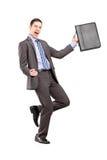 Uomo d'affari felice che tiene una cartella e che gesturing felicità Fotografia Stock Libera da Diritti