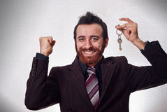 Uomo d'affari felice che tiene una chiave della casa Immagini Stock Libere da Diritti
