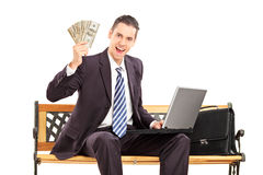 Uomo d'affari felice con il computer portatile che si siede su un banco e che tiene soldi Immagini Stock