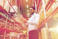 Uomo d'affari felice con il pc della compressa al magazzino Immagini Stock