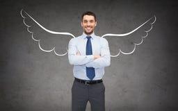 Uomo d'affari felice con le ali di angelo sopra gray fotografie stock libere da diritti