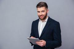 Uomo d'affari felice facendo uso del computer della compressa Fotografie Stock