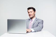 Uomo d'affari felice facendo uso del computer portatile Fotografia Stock