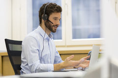 Uomo d'affari felice nell'ufficio sul telefono, cuffia avricolare, Skype immagine stock libera da diritti