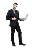 Uomo d'affari felice sorridente con il computer portatile che mostra pollice sul gesto che esamina macchina fotografica Fotografia Stock Libera da Diritti