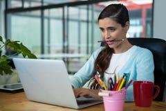 Uomo d'affari femminile che per mezzo del computer portatile allo scrittorio Immagine Stock