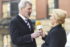 Uomo d'affari femminile di With Microphone Interviewing del giornalista Fotografia Stock Libera da Diritti