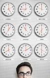 Uomo d'affari In Front Of Clocks Showing Time attraverso il mondo Immagini Stock Libere da Diritti
