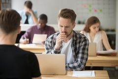 Uomo d'affari frustrato che lavora al computer portatile nel co-lavoro, pensante Immagini Stock