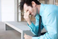 Uomo d'affari frustrato che si siede su un banco Fotografia Stock Libera da Diritti