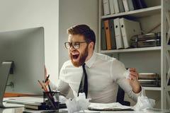 Uomo d'affari frustrato nel panico che si siede al suo posto di lavoro fotografie stock