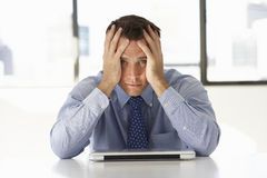 Uomo d'affari frustrato Sitting At Desk in ufficio facendo uso del computer portatile Fotografia Stock Libera da Diritti