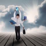 Uomo d'affari a funzioni multiple con i suoi lavori sotto cielo blu Immagine Stock