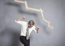 Uomo d'affari furioso davanti al grafico che indica giù. Immagini Stock