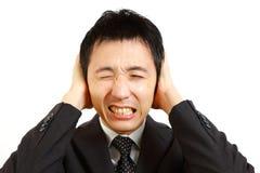 Uomo d'affari giapponese che si tiene per mano sulle sue orecchie, proteggentesi dal rumore fotografia stock