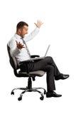 Uomo d'affari gioioso che esamina computer portatile Fotografie Stock Libere da Diritti