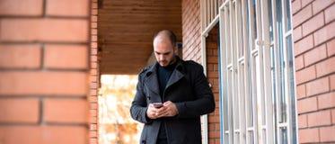 Uomo d'affari giovane che esamina il suo telefono cellulare fotografia stock