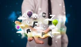 Uomo d'affari giovane che presenta le nuvole magiche con le lettere ed il bal Fotografie Stock Libere da Diritti