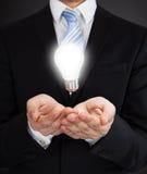 Uomo d'affari With Glowing Bulb che rappresenta le idee fotografia stock libera da diritti