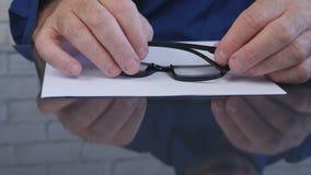 Uomo d'affari Hands Taking Eyeglasses dalla Tabella per leggere un documento immagini stock