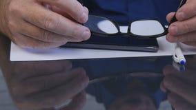 Uomo d'affari Hands Taking Eyeglasses dalla Tabella per leggere un documento immagine stock libera da diritti