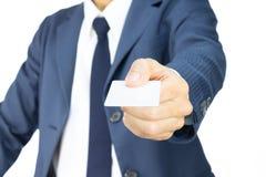 Uomo d'affari Hold Business Card nella vista diritta isolato su fondo bianco Fotografia Stock Libera da Diritti